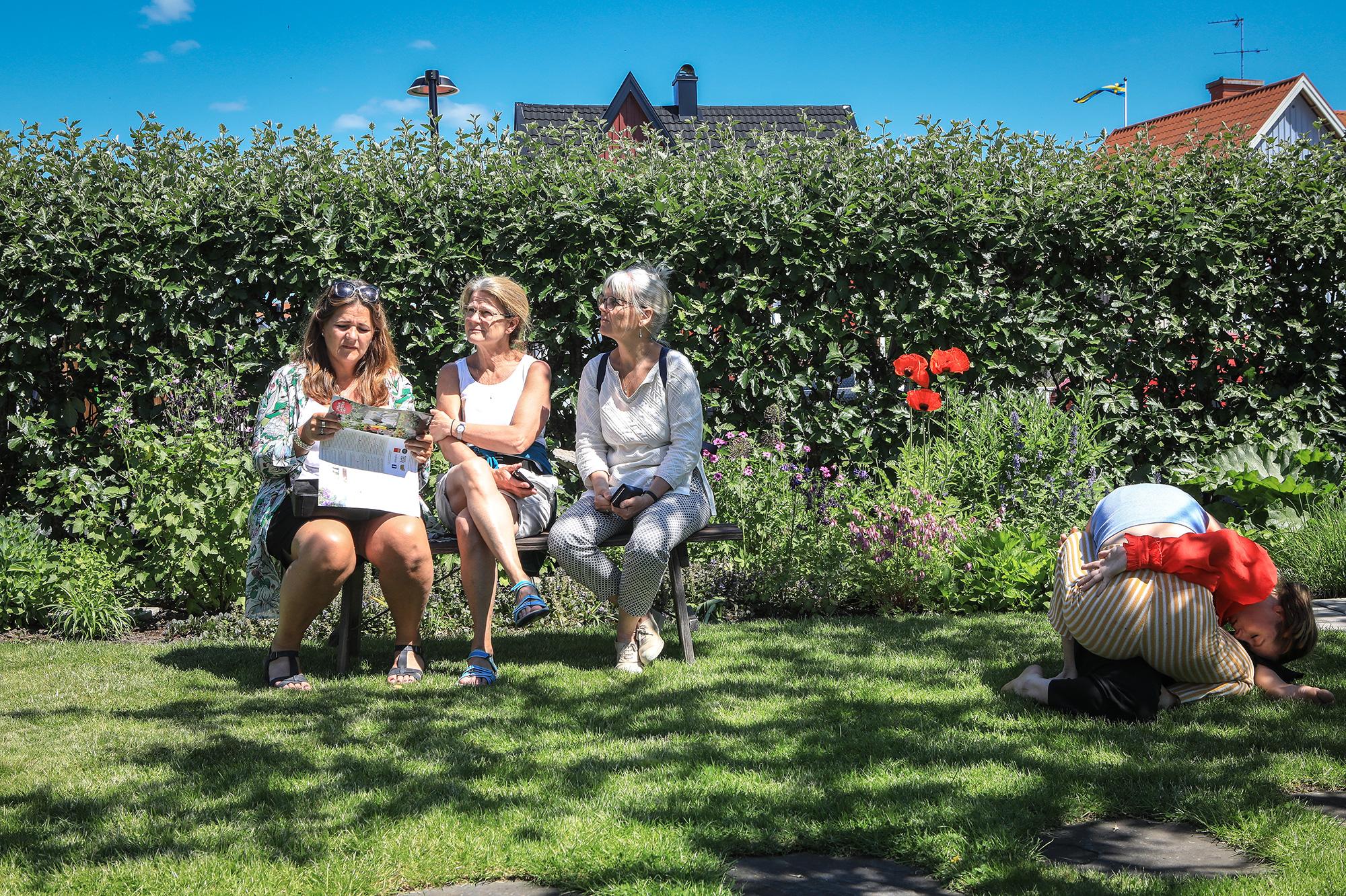 Tre trädgårdsvandrare pausar på en trädgårdsbänk.